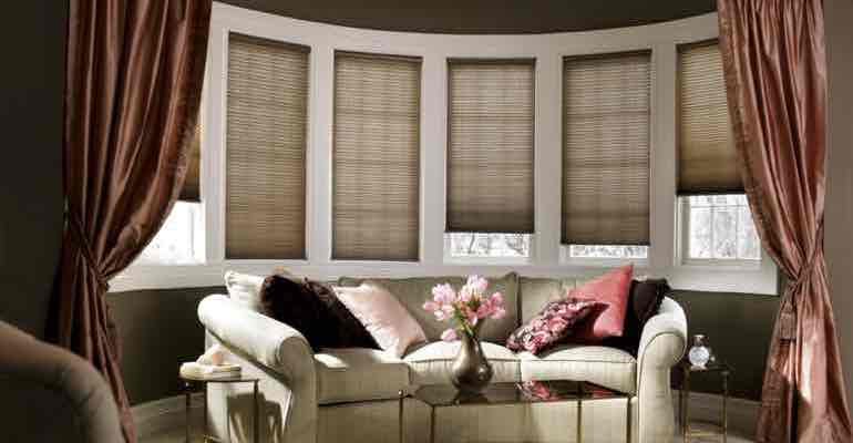 Brown honeycomb shades in lounge bow window.