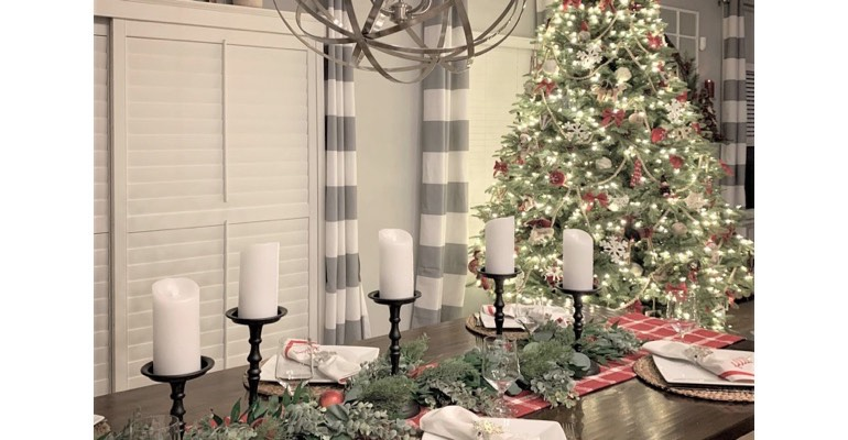 Holiday table with candles in festive dining room.