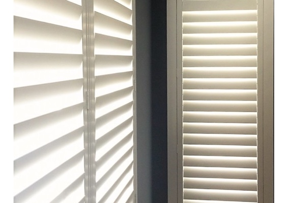 Corner plantation shutters with hidden tilt rods