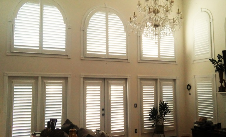 Entertainment room in open concept San Diego house with plantation shutters on arch windows.