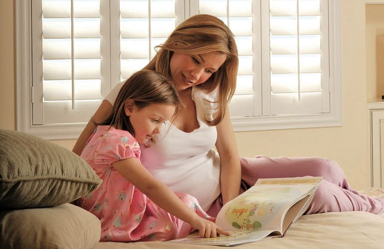 Parent and child reading on bed with shuttered windows.