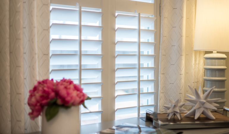 Plantation shutters by flowers in San Diego