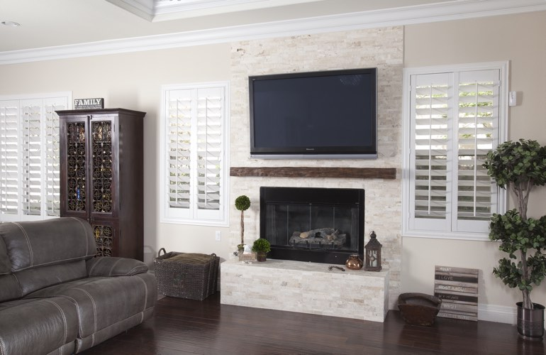 White plantation shutters in a San Diego living room with dark hardwood floors.