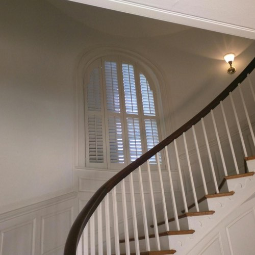 White plantation shutters adorning arched window located in spiral stairwell.