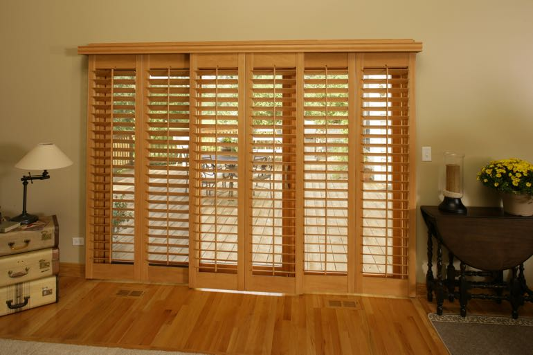 Faux wood shutters on sliding door connecting to full porch.
