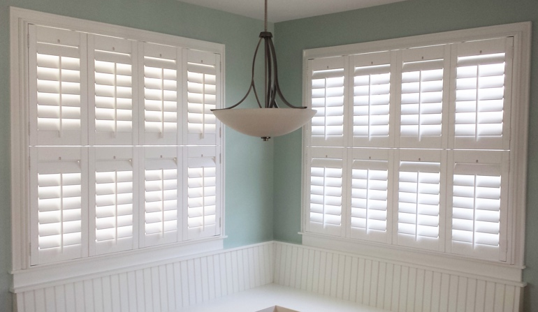 Pastel green wall in San Diego kitchen with shutters.