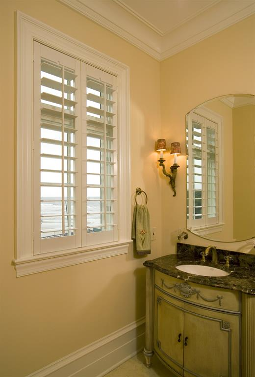 White plantation shutters in a light bathroom give a view of the ocean