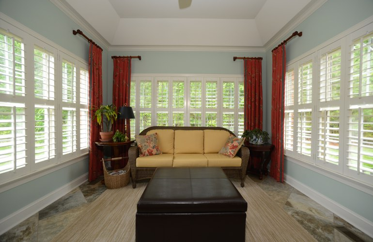 White plantation shutters in a large sunroom with robin egg blue walls
