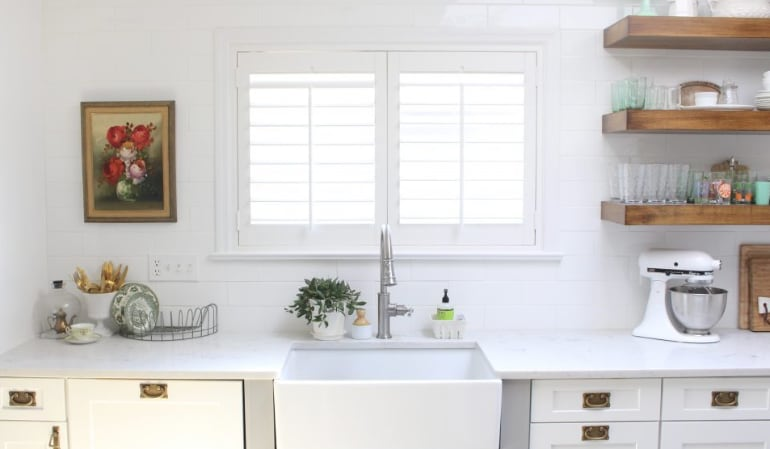 Plantation shutters over a farmhouse kitchen sink.