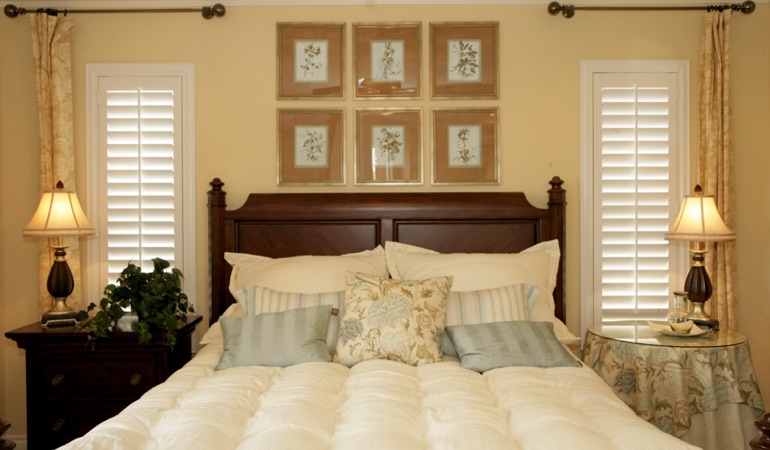 Tall plantation shutters framing bed in a bedroom in San Diego