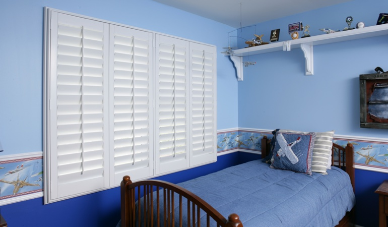 Blue kids bedroom with white plantation shutters in San Diego