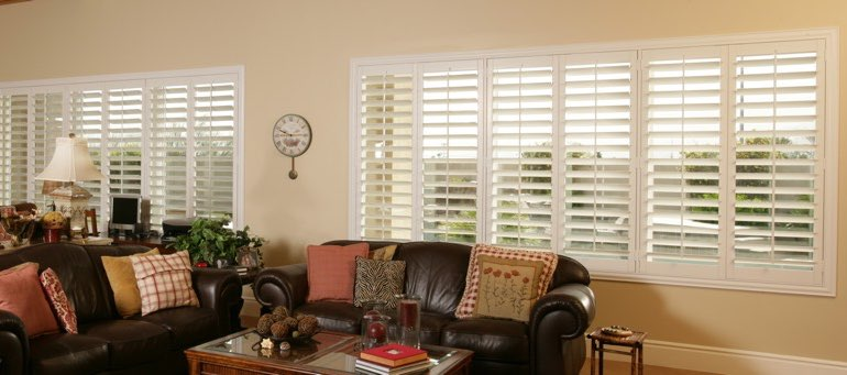Wide window with plantation shutters in San Diego living room
